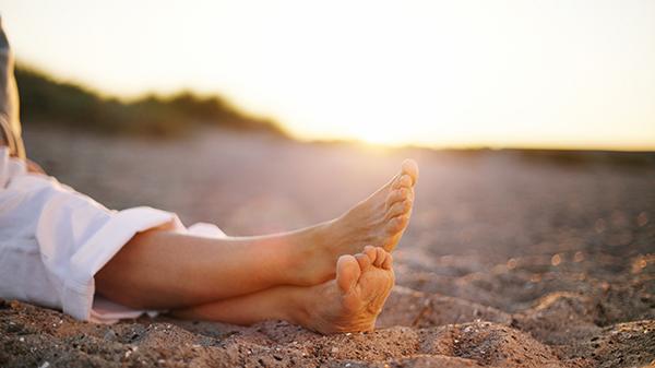 Barfota kvinnofötter på sandstrand